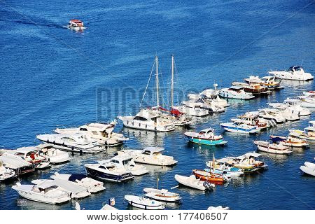 White yachts and ships of different sizes in sunny summer day