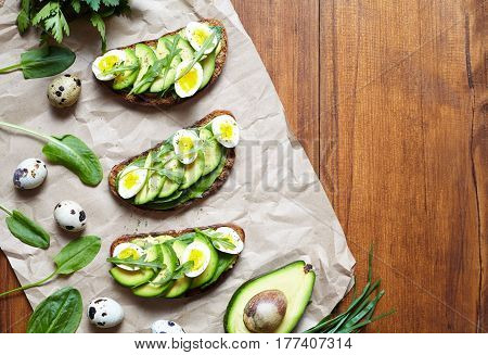 Sandwiches with guacamole, avocado, spinach, arugula and quail eggs on parchment. Low carbohydrate diet of organic products. Flat lay with copy space. Healthy breakfast concept. Spring food