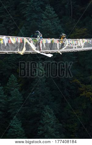 Porters carry heavy luggage on suspension bridge in Khumbu valley on a way to Everest Base camp