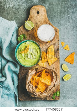 Mexican corn chips, fresh guacamole sauce in blue bowl and glass of wheat beer on rustic wooden serving board over grey concrete table background, top view