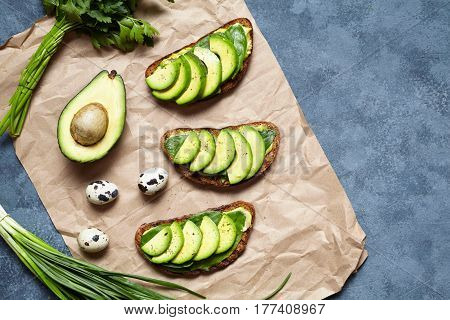 Sandwiches toast with avocado, guacamole and spinach on parchment on a concrete background. Healthy breakfast or lunch concept. Spring food mood. Flat lay food composition.