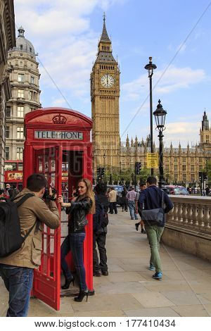 LONDON, GREAT BRITAIN - MAY 15, 2014: An unknown young couple takes a photoshoot near the most recognizable symbols of the city - Big Ben and the red telephone booth.