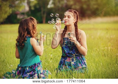 Little girls blow bubbles sitting on the grass. Two sisters