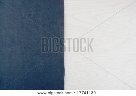 Napkin from left side white wooden table. White blue background. Blue woven linen fabric texture / white wood texture.