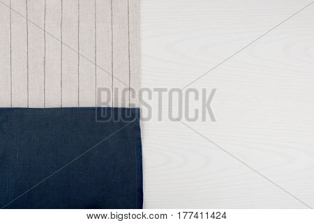 Napkin from left side white wooden table. White blue grey striped background.  Grey striped /blue woven linen fabric texture and white wood texture.