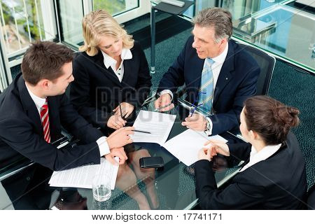 Business - meeting in an office; the businesspeople are discussing a document