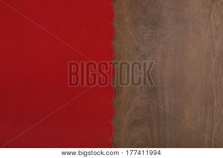 Red tablecloth from left side wooden table. Material and wood background with empty place.