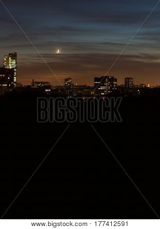 Night view of the city with abstract constructions and silhouettes of buildings. Black background copy space.