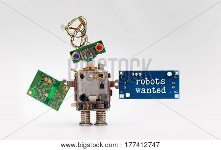 Robots wanted electronic wokers hiring concept. Toy robotic character handing circuit micro chip circuits on gray background.