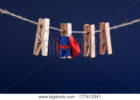 Powerful super hero conceptual photo with superstar clothespin character in blue suit red cape. leadership and wooden clothespins team at work. Dark blue background. soft focus. macro view.