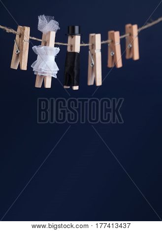 Wedding invitation card with bride and groom clothespin toys on clothesline. Abstract woman in white wedding dress and man with suit hat. Love concept photo. Macro view, shallow depth of field, copy space blue background photo