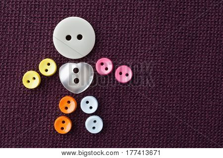Funny character made of colorful sewing buttons with love heart shape central button. violet textured textile background. macro view, shallow depth of field photo