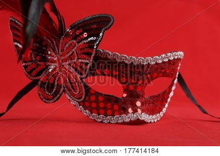 Carnival mask with butterfly and feathers. Red glossy mask on red background.
