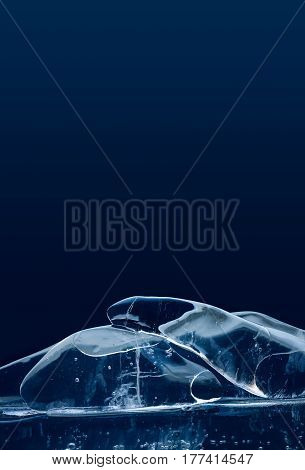 Stylish artistic piece of ice on blue background. Macro view transparent glacial crystal gems objects. Frozen water abstract shapes, soft focus. copy space.