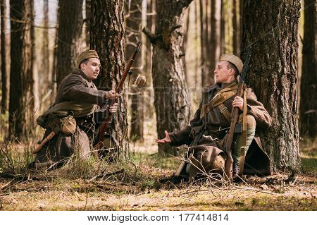 Pribor, Belarus - April 23, 2016: Two Re-enactors Dressed As Russian Soviet Infantry Soldiers Of World War II Hidden Sitting With Rifle Weapon In An Ambush Near Tree In Spring Forest