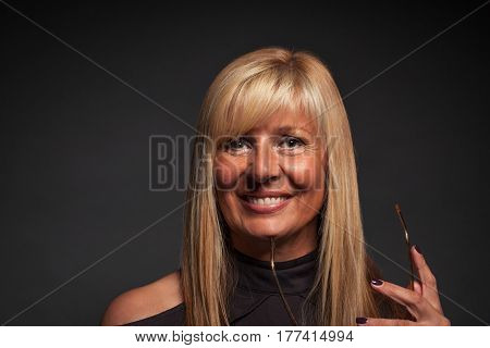 Beautiful mature woman holding glasses against her chin