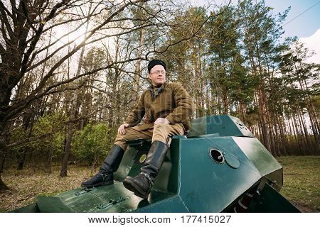 Pribor, Belarus - April 23, 2016: Re-enactor Dressed As Russian Soviet Soldier Of World War II Sitting In Armoured Soviet Scout Car BA-64 In Forest.