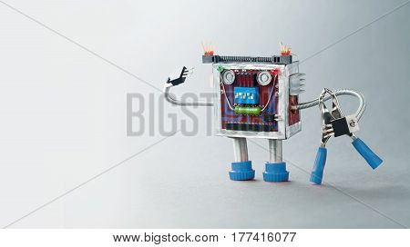 Electrician robot ready for work. Serviceman toy character with blue pliers. Gray background photo.