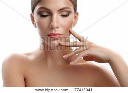 Bronzed beauty. Beautiful young woman with perfect skin touching her face sensually isolated on white beauty cosmetology cosmetics sensuality sexuality concept copyspace