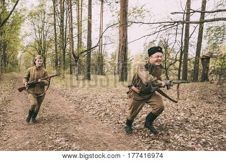 Pribor, Belarus - April 24, 2016: Woman And Man Re-enactors Dressed As Soviet Russian Red Army Infantry Soldiers Of World War II Running In Attack With Rifle In Forest At Spring Season.