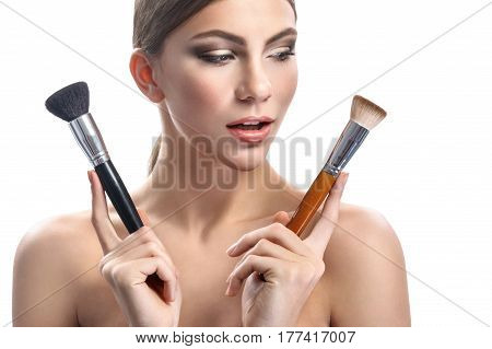 For flawless makeup. Beautiful young woman with professional makeup holding two makeup brushes to choose isolated on white profession stylist fashion beauty salon visage maquillage concept