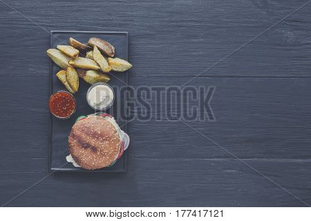 Burger and wedges, restaurant dish top view with copy space. Meat cheeseburger in craft paper, potato chips. Take away set on dark black wood background. Hamburger and spicy tomato sauce.