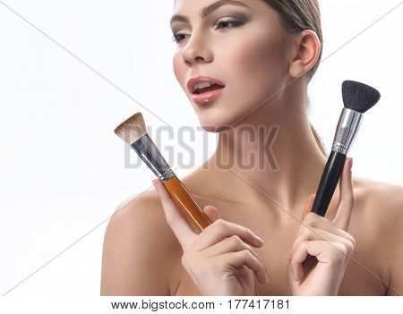 Accentuated beauty. Close up shot of a stunning young beautiful fashion model with smoky eyes makeup and nude lip gloss looking away holding makeup brushes next to her face copyspace