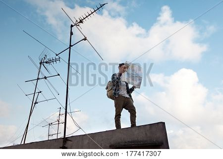 Young traveler standing at the edge of the roof in the city with map in hands