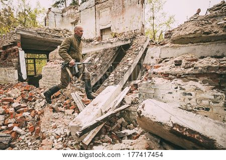 Pribor, Belarus - April 24, 2016: Re-enactor Dressed As Soviet Russian Red Army Infantry Soldier Of World War II Is Running In Attack With Submachine Gun Along Rubble Of Building