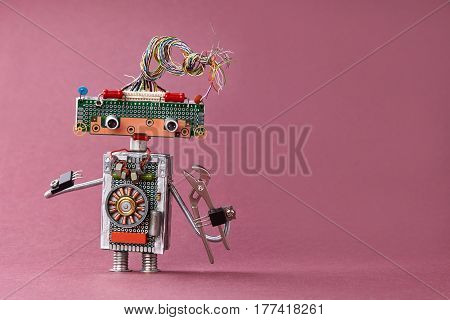 Creative design toy electrician pliers in hand. Colorful robot with electric wires hairstyle, electronic circuits, chip capacitors vintage resistors. Violet background copy text