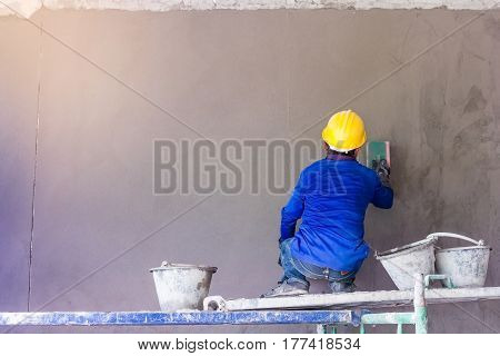 Construction worker using trowel plastering concrete during wall covering works with self-levelling cement mortar