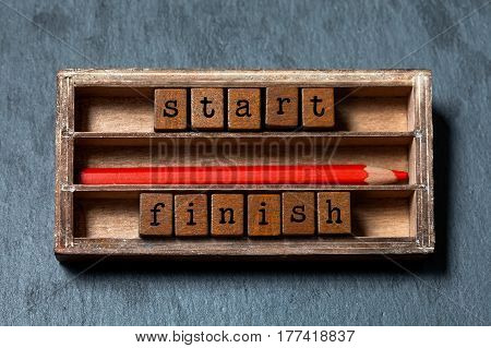 Start finish concept. Vintage box, wooden cubes phrase with old style letter, red pencil. Gray stone textured background. Close-up, up view, soft focus