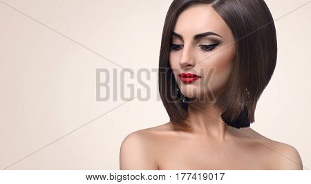 Young fashion model posing sensually looking away wearing black dress and evening makeup with red lips and smoky eyes copyspace beauty fashion style elegance cosmetics concept.