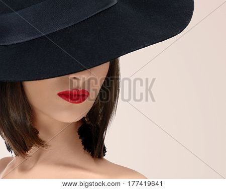 Cropped close up of a red lipped young woman posing seductively wearing a hat hiding her face copyspace beauty cosmetics skincare cosmetology face red lips lipstick fashion style vintage retro.