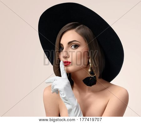 Close up studio portrait of a fashionable young woman wearing professional makeup modeling fashion clothing shushing to the camera expressive shush quiet beauty secret cosmetics stylish .