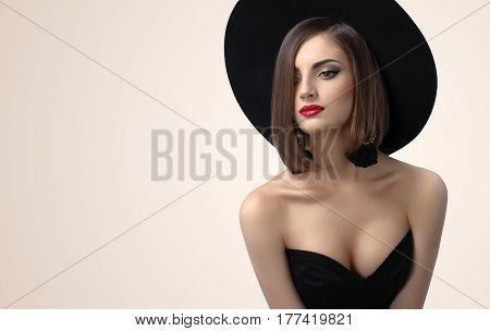 Stunning sexy red lipped brunette wearing a hat and black corset posing seductively in studio copyspace sexy erotic beauty makeup seduction femininity cosmetics body concept poster