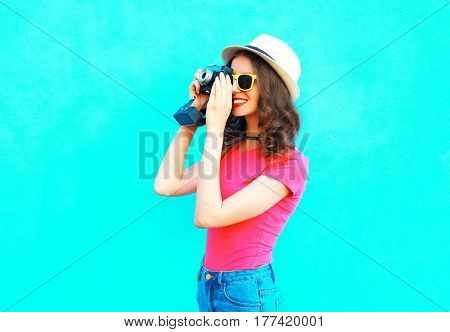 Fashion Pretty Woman Taking Picture Wearing Straw Summer Hat, Sunglasses And Vintage Camera Over Col