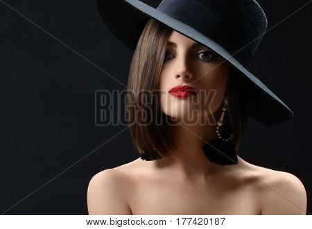 Close up studio shot of a stunning beautiful red lipped young female wearing a hat looking to the camera confidently copyspace makeup cosmetics beauty shadow mystery fashion concept .