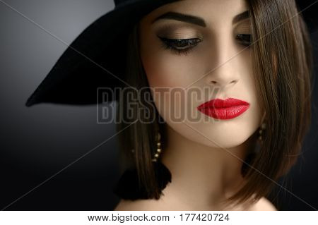 Cropped close up of a sexy red lipped elegant brunette in a hat posing sensually looking away beauty makeup cosmetics red lips seduction seductive retro vintage luxury fashion classy concept.