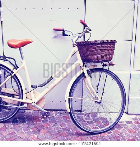 White bicycle with classic basket on the street of European town. Filtered image.