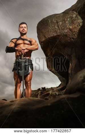 On guard of peace. Vertical full length shot of a muscular warrior standing with a sword on a rock looking away