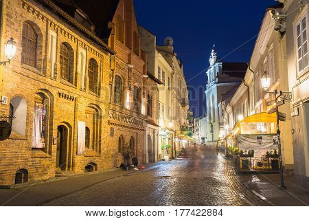Vilnius, Lithuania - July 8, 2016: Illuminated Facades Of Ancient Buildings On Famous Pilies Street Of Old Town In Night, Popular Showplace Under Summer Dark Blue Sky.