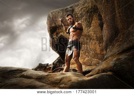 Ancient God. Shot of a brave masculine warrior pointing his sword at the camera standing on a rock peak