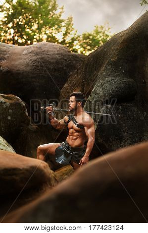 Brave fighter. Vertical portrait of a young warrior with muscular body holding his sword resting in the woods