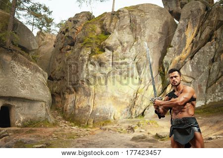 Always ready. Horizontal shot of an ancient warrior posing with a sword near the rocks outdoors copyspace
