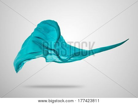 Smooth elegant blue transparent cloth separated on gray background. Texture of flying fabric.