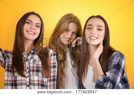 Beautiful young women taking selfie on color background