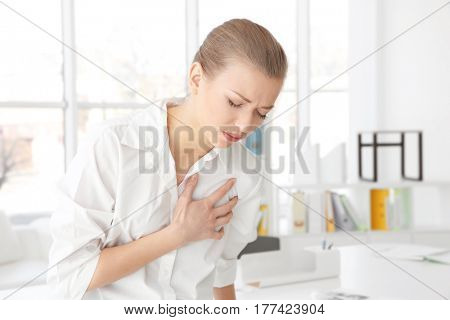 Heart attack concept. Young woman suffering from chest pain in office