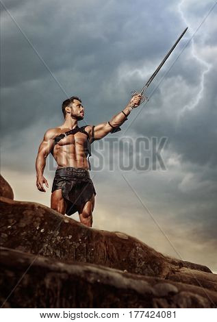 Proud warrior. Vertical low angle shot of a strong muscular Spartan warrior pointing his sword at the grey stormy skies