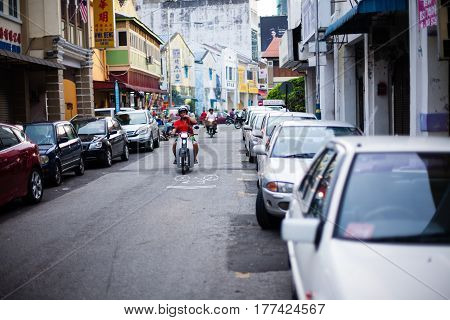 Penang, Malaysia - October 19, 2014: Architecture narrow streets with people on motocycle. Dirty moldy humidity cityscape